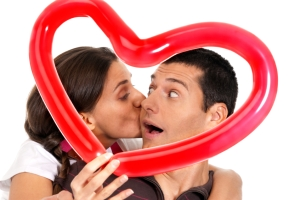 Young couple kissing through balloon heart surprise isolated